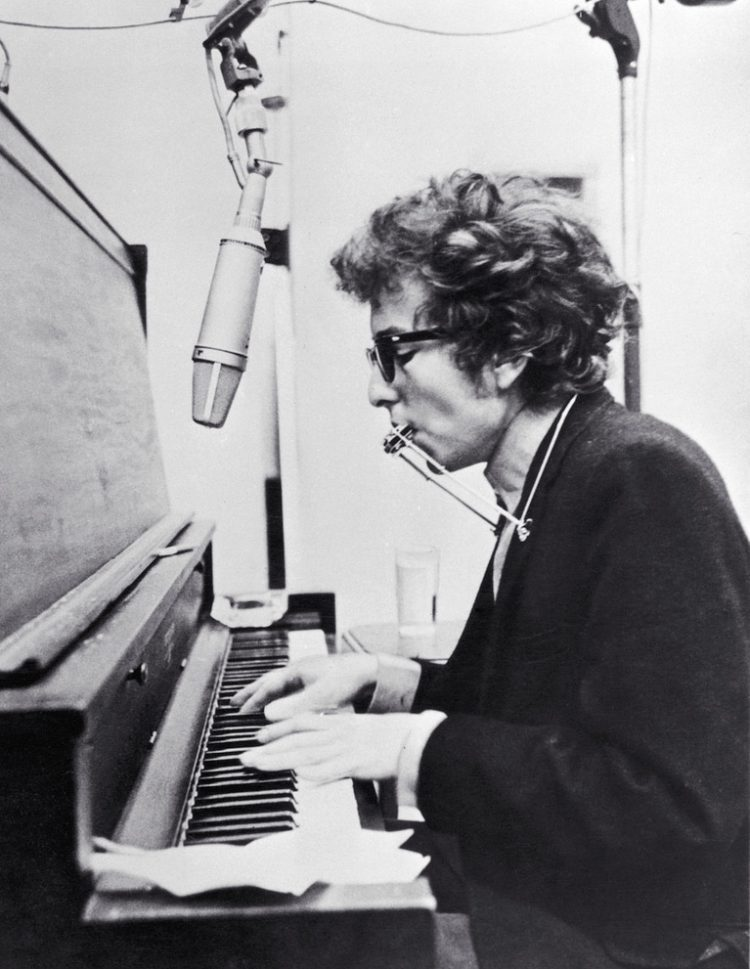 circa 1965:  American rock singer and songwriter Bob Dylan playing the piano and the harmonica simultaneously with the use of a harmonica holder.  (Photo by Hulton Archive/Getty Images)